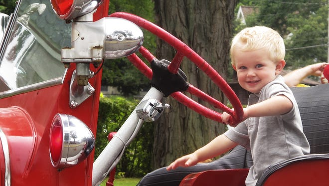 Nicholas Youngs, of Elmira, checks out a fire truck during the 2013 Olde Tyme Summer Festival.