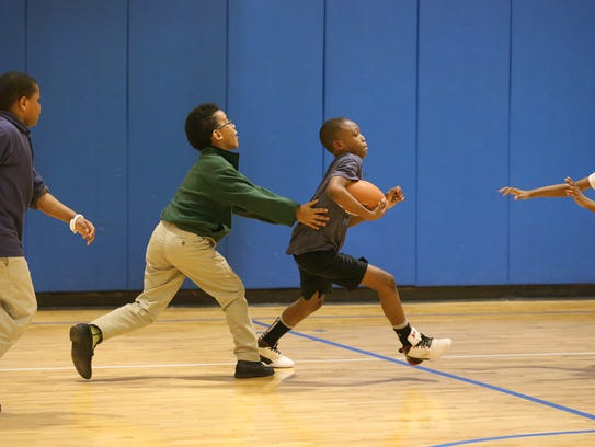 Anttwan Brown, center, plays football in the gym with