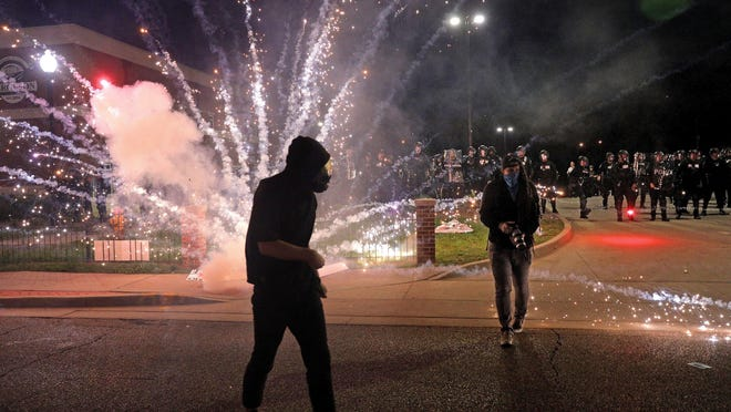 Fireworks thrown by protesters explode outside the Ferguson police department on Sunday. As protests rage across the country, questions about the deaths of six people affiliated with the 2014 protests in Ferguson are resurfacing. Here's what we know.
