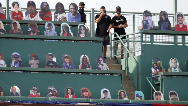 Boston Red Sox employees stand in the Green Monster seats with cutouts of former players and fans before the opening day game against the Baltimore Orioles at Fenway Park in Boston Friday.