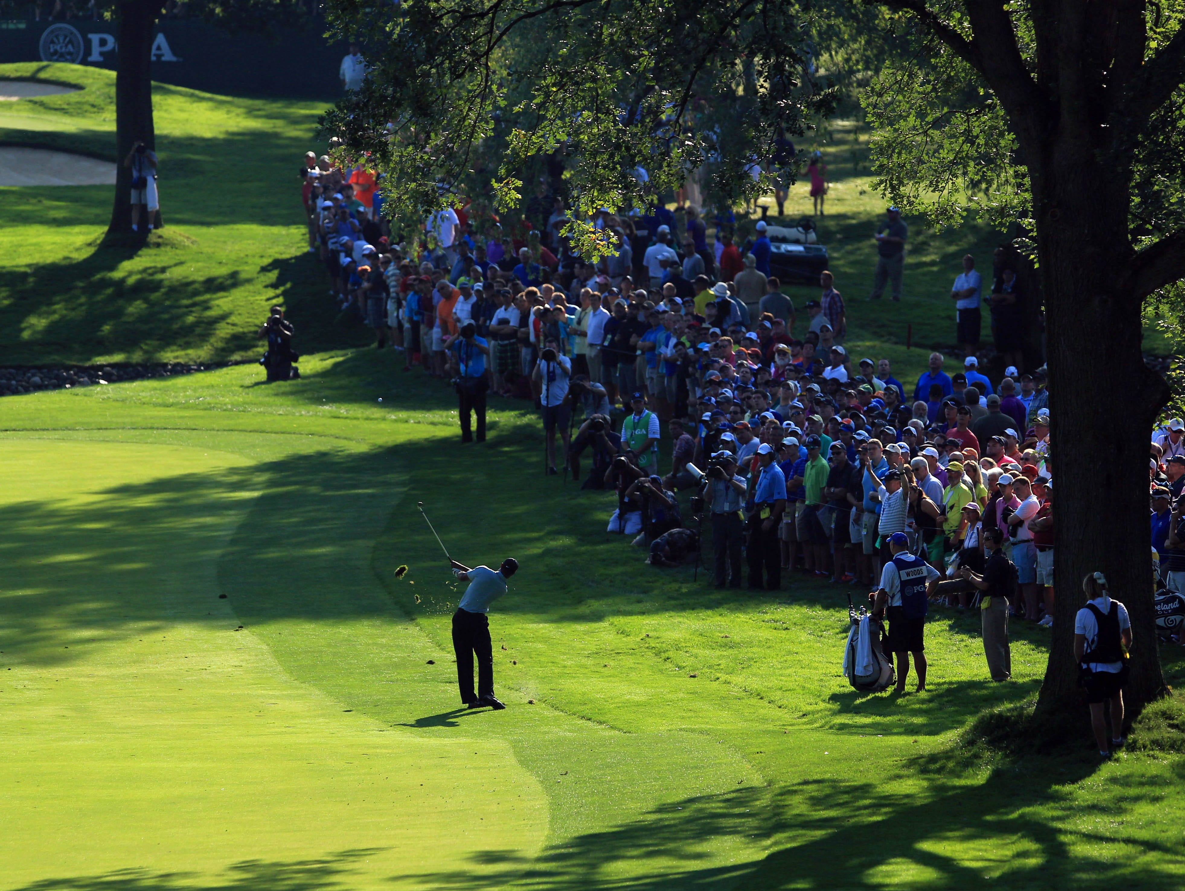 Tiger Woods plays a shot on the 10th hole during the first round of the 95th PGA Championship at Oak Hill Country Club.