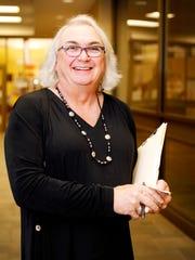 Marcie Bernardo holds paperwork from an informational