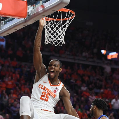 Clemson forward Aamir Simms (25) reacts after dunking