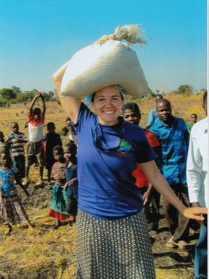 Jessi Stitt, missionary from Black Mountain tries her talent for balancing a bag of grain on her head.