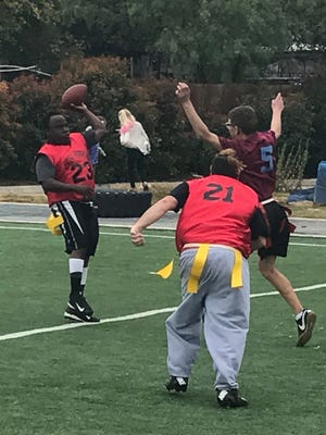 Johnny Wilson passes while Josh Deluna applies pressure Saturday at the Special Olympics flag football tournament.