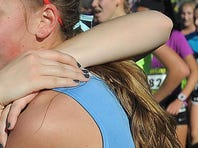 Sioux Falls Lincoln Patriots embrace after running in the Girls' Championship 5000m during the Nike Cross Nationals Heartland Regional at Yankton Trail Park on Sun., Nov. 15, 2015.