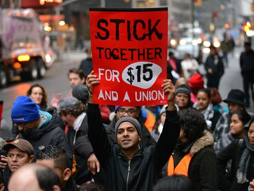 A protester in New York holds up a placard as fast-food workers and union members call for an increase in the minimum hourly wage to $15 and the right of workers to join unions.