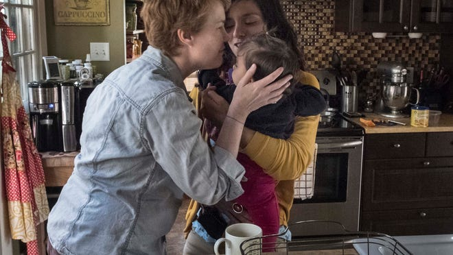 Sophy Jesty, left, and Valeria Tanco kiss their 1-year-old, Emilia, at their home in Knoxville. The couple married in New York in 2011.