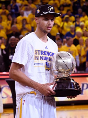 Golden State Warriors guard Stephen Curry (30) celebrates with the western conference championship trophy.