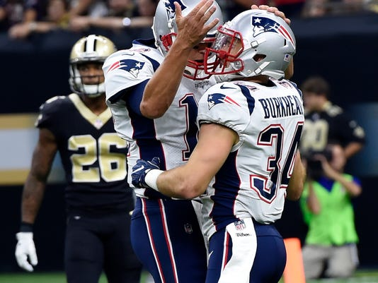 New England Patriots running back Rex Burkhead (34) celebrates his touchdown with quarterback Tom Brady in the first half of an NFL football game against the New Orleans Saints in New Orleans, Sunday, Sept. 17, 2017. (AP Photo/Bill Feig)