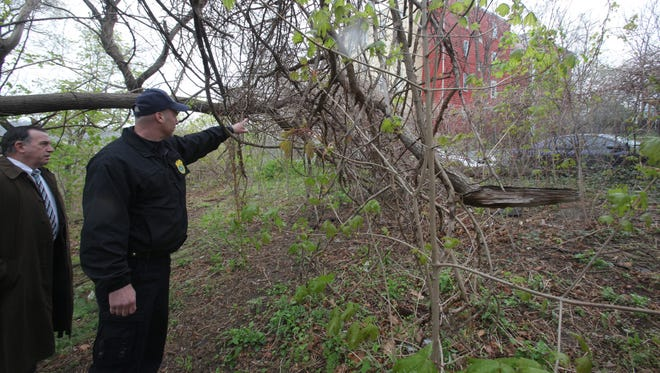 From left Yonkers Detective Vincent DiDio looks as SPCA of Westchester Director Ernest Lungaro shows him where 25 dead cats were found in Yonkers on  April 29, 2014.