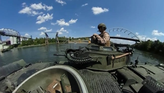 Gunnery Staff Sgt. Michael Espinoza, an amphibious assault commander with 2nd Battalion, 6th Marine regiment directs his crew as they operate their AAVs along the Cumberland River as part of Nashville's Marine Week on Thursday Sept. 8, 2016.