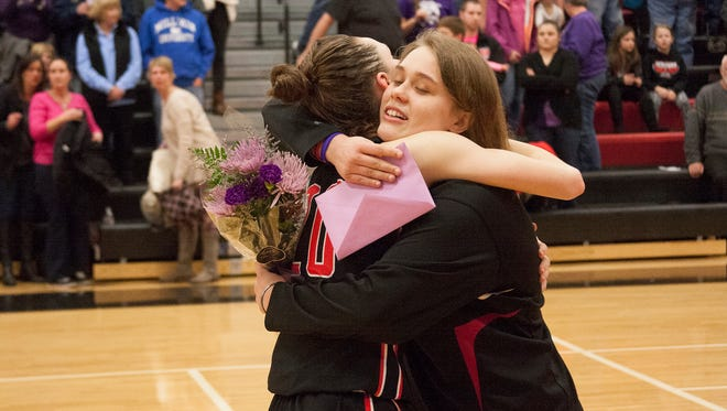Jackson Northwest senior Nicole Keeder gives Marshall sophomore Maddie Reynolds a card and a hug Friday evening.
