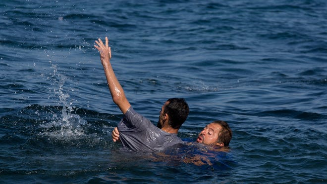 Local resident Dimitris Karapanagiotis, right,  rescues an Afghan migrant whose boat stalled at sea while crossing with others from Turkey to the island of Lesbos, Greece, on Saturday, Sept. 19, 2015.