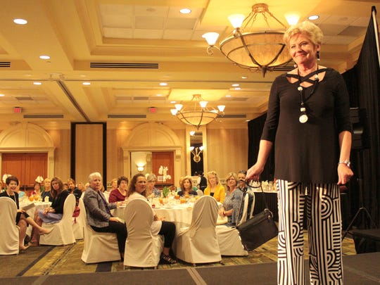 Sue Goldsberry shows off a black cross neck top with pinstripes inspired pants. Goldberry is a donor and social chair of the Ohio State Alumni Club of Naples.