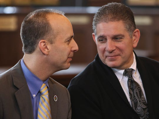 Lansing Mayor Mayor-Elect Andy Schor looks at his predecessor, Mayor Virg Bernero, during a press conference on Monday, December 18, 2017.