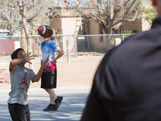 Juan Sosa, 10, plays catch with Marcel Nicolitz, a