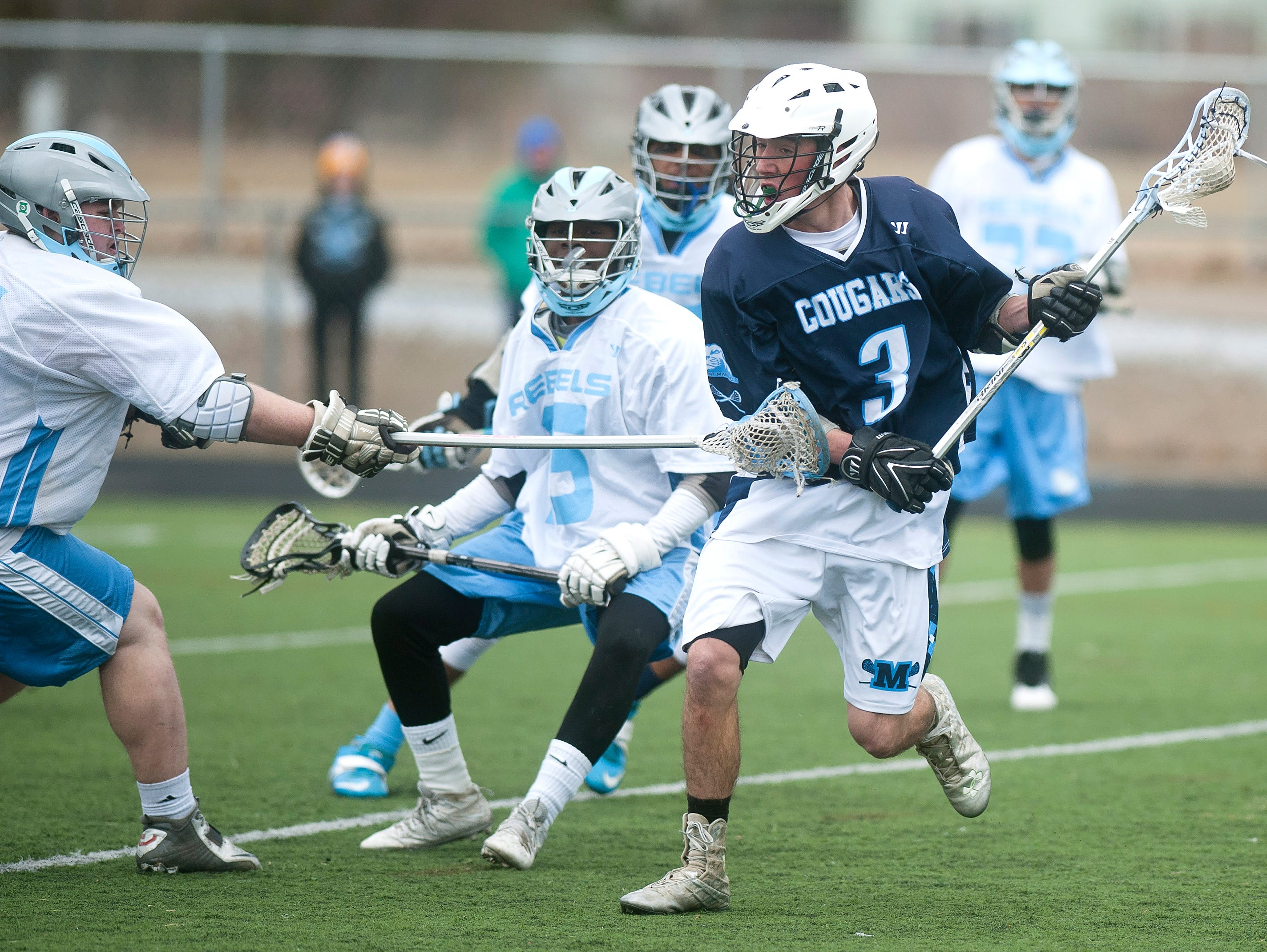 Mount Mansfield's Josh Brown, right, plays through a check from a South Burlington defender during Saturday's game.