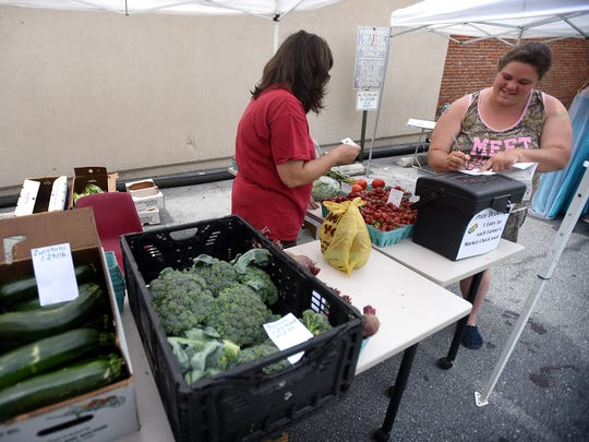 Tina Forry, of Risser-Marvel Farm Market in South Londonderry Township, sells farm fresh produce to Veronica Englehart of Lebanon Wednesday, June 15, 2016, at the Farm to Table event, sponsored by Lebanon Family Health Services, 615 Cumberland St., Lebanon.