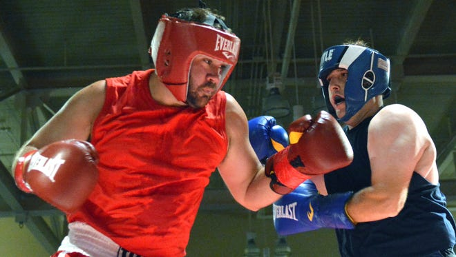 """Joseph Lee (red) representing the Las Cruces Fire Department and Mannie Sanchez (blue) reprenting the Las Cruces Police Department squared off for the 2017 """"Battle of the Badges"""" boxing event."""