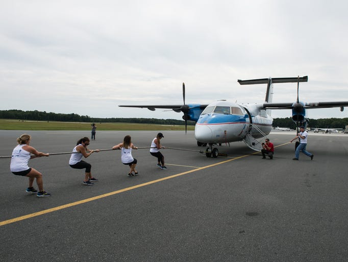 A team pulls a Dash-8 aircraft during Piedmont Airlines