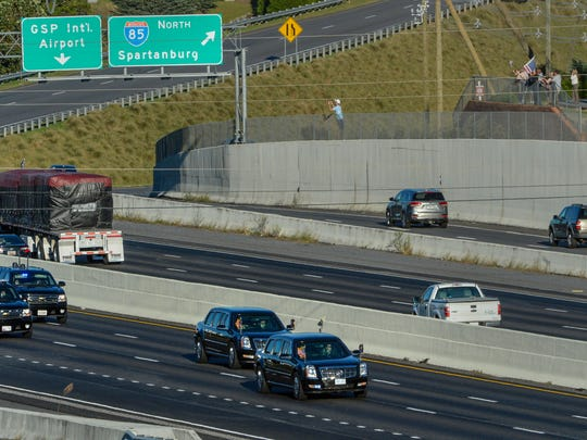Bystanders wave a U.S. flag on the Northbound side of I-85 while the U.S. Presidential motorcade drives South near State Highway 14 in Greenville on Monday.
