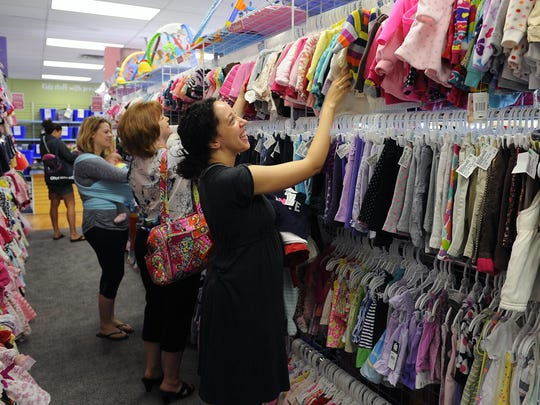 Customers shop for children's clothing at the grand opening of the Once Upon A Child store in Delta Township today.