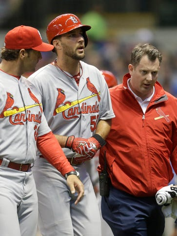 Adam Wainwright (50) is helped off the field after