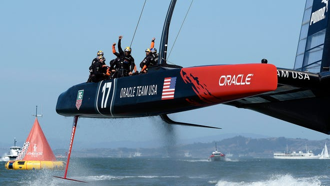Oracle Team USA members react after crossing the finish line to win Race 17  against Emirates Team New Zealand in the America's Cup Finals Tuesday. The winner-take-all race will be Wednesday.