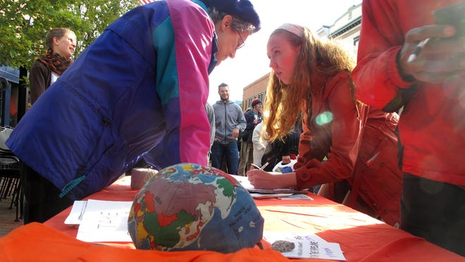 Louise Brill, left, of Burlington, a volunteer with 350Vermont, discusses a statewide carbon tax Wednesday with Champlain College student Haley Parent. Parent ultimately signed a petition calling for legislative action.