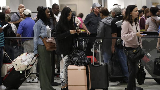 Passengers wait in line at a security checkpoint at Miami International Airport, Friday, Jan. 18, 2019, in Miami. The three-day holiday weekend is likely to bring bigger airport crowds.