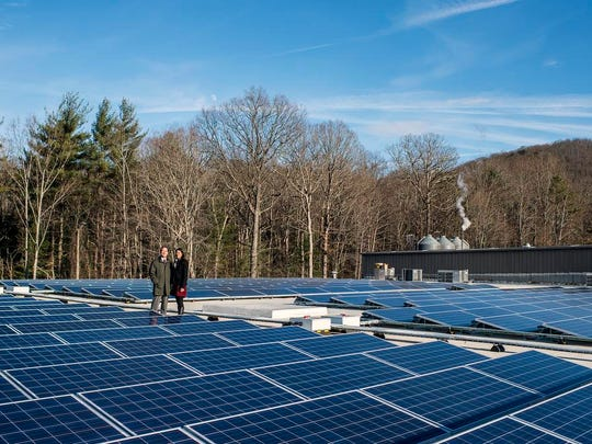 Oscar Wong and Leah Wong Ashburn stand around the newly installed and functioning solar panels on the rooftop of Highland Brewing in Asheville. The brewery currently powers all of its production with the panels, and Ashburn said she hopes to power everything in their building with solar energy.