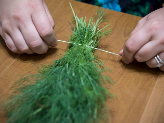 Katie Sims prepares a bundle of dill to hang in her kitchen on Wednesday, June 29.