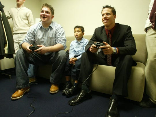Brian Roche, left, and Brian Cushing, right, play a video game before making their college announcements on national television.