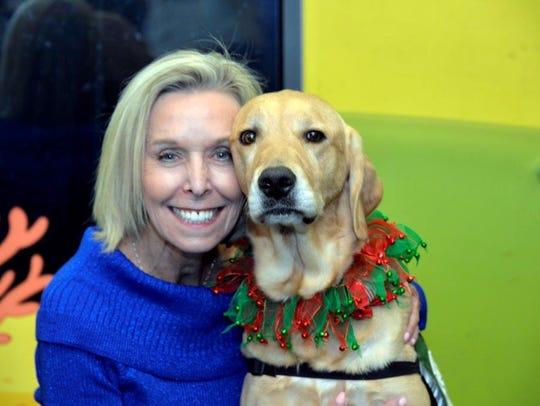 Beverly Eye, with one GHS's therapy dogs, works to