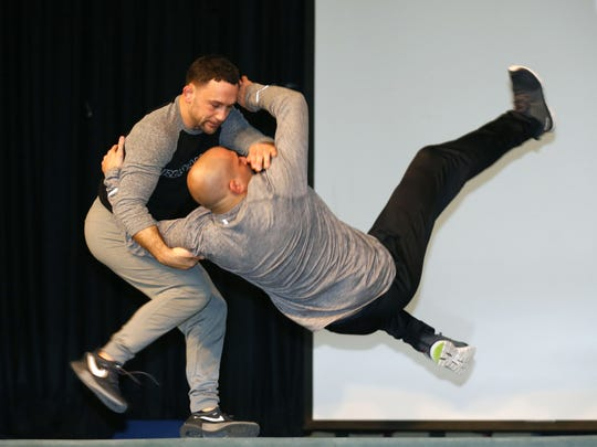 UFC fighter Frankie Edgar, flips Brick Memorial assistant principal Dan O'Cone during an exhibition at Ocean County Prosecutor's forum held at Brick Township High School about the opiate and heroin drug epidemic facing the region.