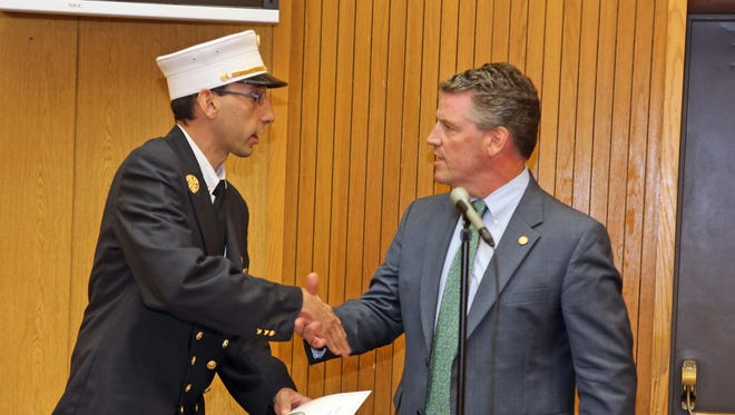 New York State Senator Terrence Murphy presents a proclamation to Andrew Seicol, Chief of the North White Plains Fire Department during a ceremony honoring first responders to last February's Metro-North train crash in Valhalla at Mount Pleasant Town Hall July 14, 2015.