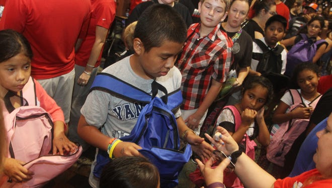 FILE: Billy Aguilar, 11, center, and thousands of other students packed Harborside Event Center in Fort Myers to get free school supplies at last years event.
