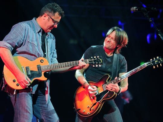 Hosts Vince Gill, left, and Keith Urban perform together