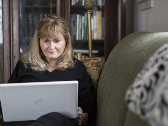 Billie Travalini writes on her couch in her home in
