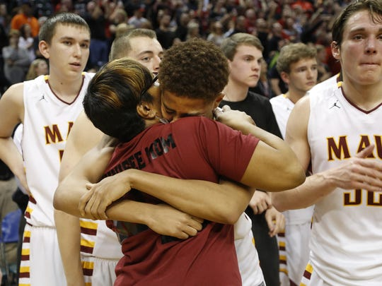 Robert Phinisee is embraced by his mother, Tanika, moments after McCutcheon lost to New Albany 62-59 in the Class 4A state championship Saturday, March 26, 2016, at Bankers Life Fieldhouse in Indianapolis.