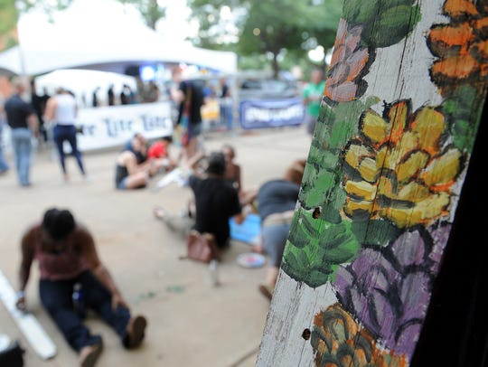 A fence post covered in painted flowers is left to dry for the Wichita Falls Alliance for Arts and Culture's Don't Fence Me In community art project Saturday, June 24, 2017, at the Art and Soul Festival at the Wichita Falls Downtown Farmers Market and Ohio Street. This year's event will be 1 to 10 p.m. June 23, 2018.