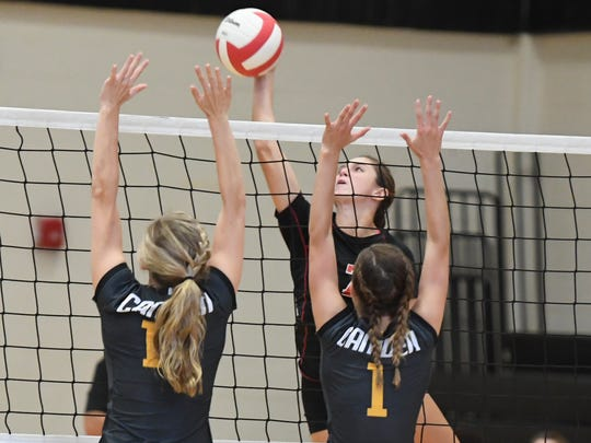 South Side's Ashlynne Clifft spikes the ball over Camden's Sydney Baker and Jordan Vick during a game last season. Camden won 3-0.