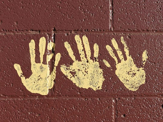 Sparks Middle School shooting surviors, Justin Fuentes, left, Neil Penrod, center, and Elizabeth Long, leave their hand prints on a Sparks High wall, a tradition at the school. All three were students at Sparks Middle when in 2013 a student killed a teacher and himself.