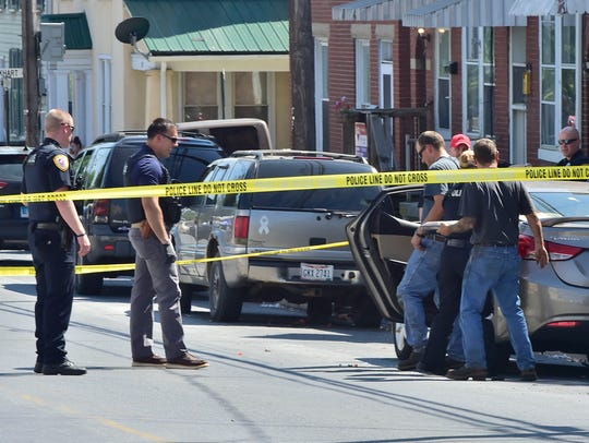 Police investigate at the scene of the shooting in the unit block of South Franklin Street on Thursday afternoon.