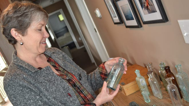 Sarah Thomas holds one of the bottles she and her husband discovered under the floorboards when they were remodeling a family Lakeside cottage.