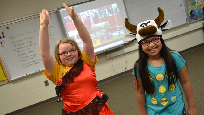 Maci Mowery, left, shows off her moves as a flamenco dancer, while Alessia Moya dressed as a bull at the Spanish Summer Camp.