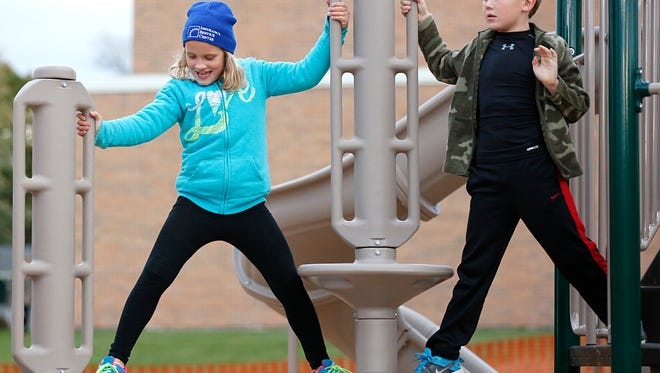 Second-graders Brittany Reilly and Jace Goebel climb on new playground equipment during a grand opening celebration held Oct. 13 at  Eden Elementary School.