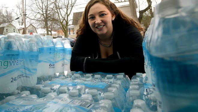 Lansing resident Carrie Davis, 29, stands by the trunk of her car Friday afternoon while it's packed with 20 cases of bottled water. She started an online fundraiser to buy bottled water for Flint residents that has raised nearly $14,000 in a week.