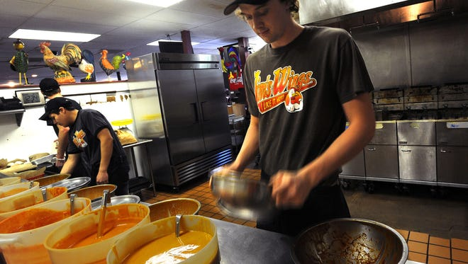 Jim's Wings employee Phil Wells shakes a bowl of wings, coating them in sauce in Fort Collins in 2013.
